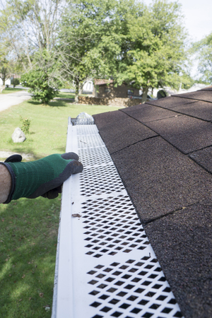 installation of plastic leaf guards on a gutter